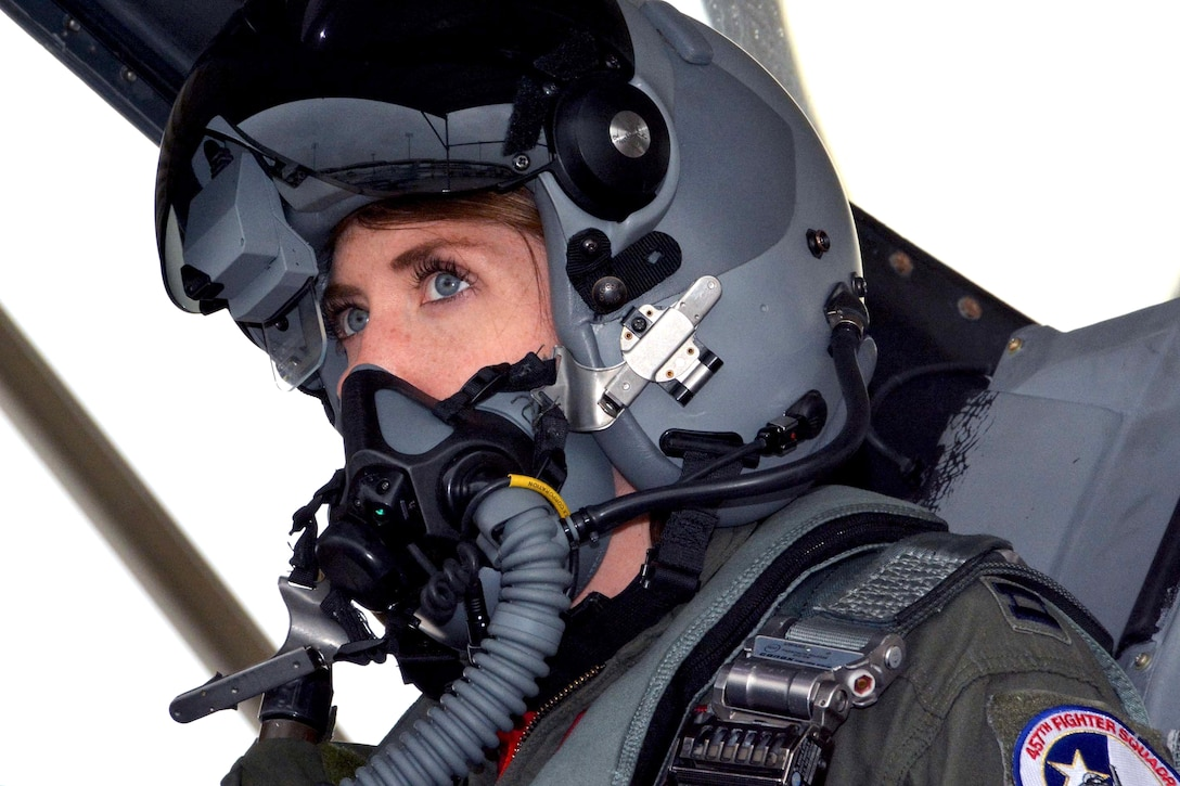A pilot looks forward while sitting in a cockpit.