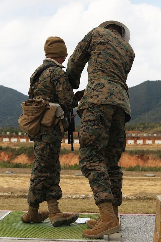 CAMP SCHWAB, OKINAWA, Japan – A range coach helps a Marine adjust her shooting stance on rifle range Feb. 14 aboard Camp Schwab, Okinawa, Japan.