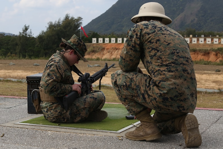 CAMP SCHWAB, OKINAWA, Japan – A range coach observes as a Marine preforms remedial action to remove a jammed round on the rifle range Feb. 14 aboard Camp Schwab, Okinawa, Japan.