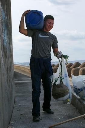 Lance Cpl. Victor Diaz carries the trash he found during a beach cleanup Feb. 24 at Sunabe Seawall, Okinawa, Japan. Twenty-one Marines with the Single Marine Program from Camp Courtney visited the seawall to help clean up debris along the beach. Diaz is a network administrator with Headquarters Battalion, 3rd Marine Division. (U.S. Marine Corps photo by Pfc. Nicole Rogge)