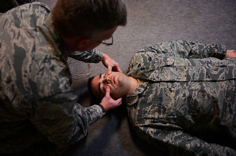 U.S. Air Force Capt. Jeremy Bull, 313th Expeditionary Operations Support Squadron flight nurse, demonstrates self-aid buddy care techniques on U.S. Air Force Tech. Sgt. Peter Salas, 313th EOSS systems administrator, during a training day on Ramstein Air Base, Germany, Feb. 16, 2018. The 313th EOSS is part of the 721st Air Mobility Operations Group, which supported more than 4,500 aircraft coming through Ramstein over the past year. (U.S. Air Force photo by Senior Airman Joshua Magbanua)