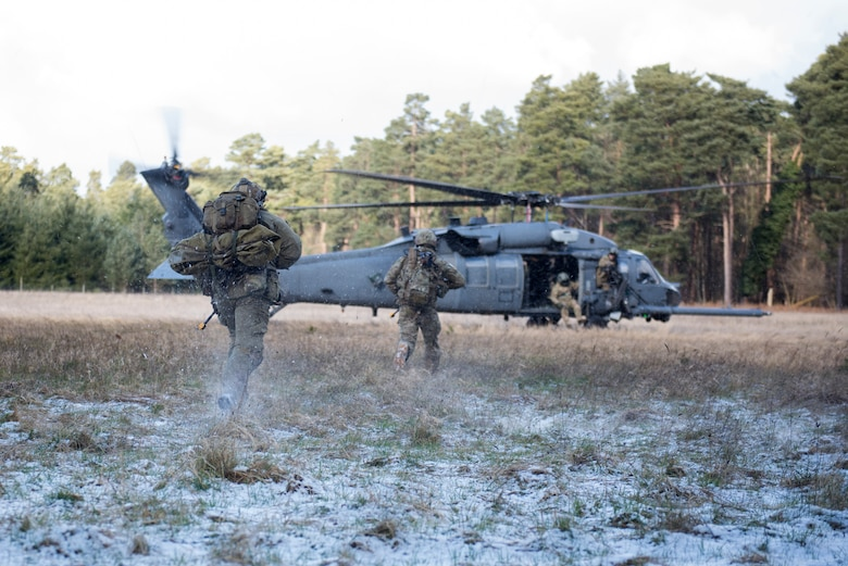 Pararescuemen assigned to 57th Rescue Squadron dash toward a 56th RQS HH-60G Pave Hawk during a training scenario for exercise Point Blank at the Stanford Training Area, England, Feb. 27. Point Blank is a low-cost initiative designed to increase tactical proficiency of Department of Defense and Ministry of Defence forces stationed within the United Kingdom and Europe. (U.S. Air Force photo/Senior Airman Malcolm Mayfield)