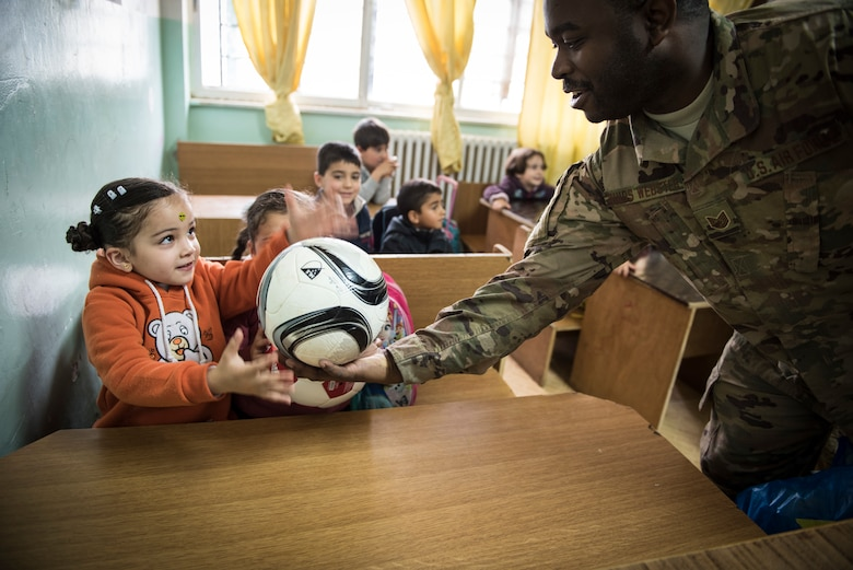 Tech. Sgt. Darren Hinds-Webster, assigned to the 332d Mission Support Group, hands out soccer balls to school children during a donation drop-off February 26, 2018, at an undisclosed location. Service members reached out to family and friends back home and were able to provide school supplies and soccer balls to two local schools, as well as clothing, books, and hygiene products for refugees in the region. (U.S. Air Force photo by Staff Sgt. Joshua Kleinholz)