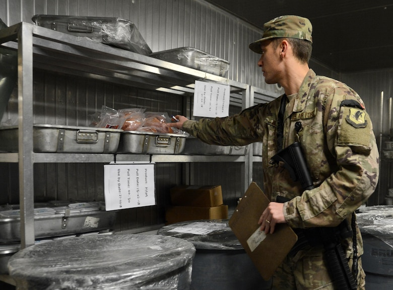 Staff Sgt. Nikola Bozic, 455th Expeditionary Medical Group public health technician, checks for expired food during his routine food inspection of the Grady dining facility Feb. 15, 2018 at Bagram Airfield, Afghanistan.