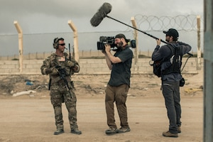 A man holding a camera and a man holding a large mic talk to a service member.