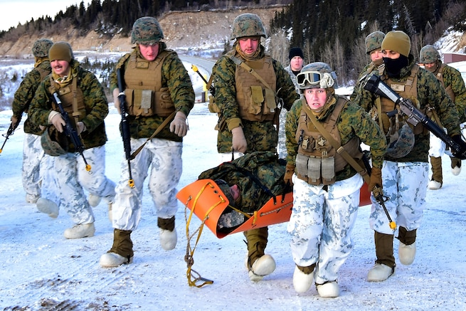 Marines in cold-weather gear carry a mock patient in an orange stretcher.