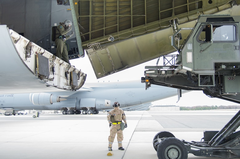 Team Dover Airmen offload a C-5M Super Galaxy wearing full MOPP gear during the 2018 Vengeant Eagle Exercise Feb. 22, 2018, at Dover Air Force Base, Del. One of the many tasks during the exercise was to land and offload cargo in a simulated contaminated environment. (U.S. Air Force photo by Mauricio Campino)