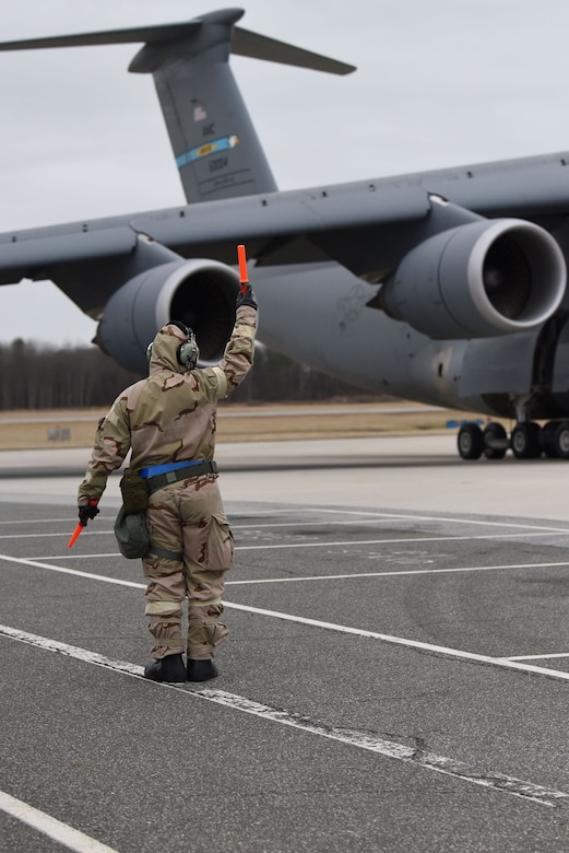 Staff Sgt. Nikko Kuusinen, a 436th Aircraft Maintenance Squadron, C-5M Super Galaxy crew chief, marshals in a C-5M during the 2018 Exercise Vengeant Eagle Feb. 22, 2018. Airmen performed their jobs in Mission Oriented Protective Posture, MOPP, gear the same way they would on a regular day. (U.S. Air Force photo by Airman 1st Class Zoe M. Wockenfuss)