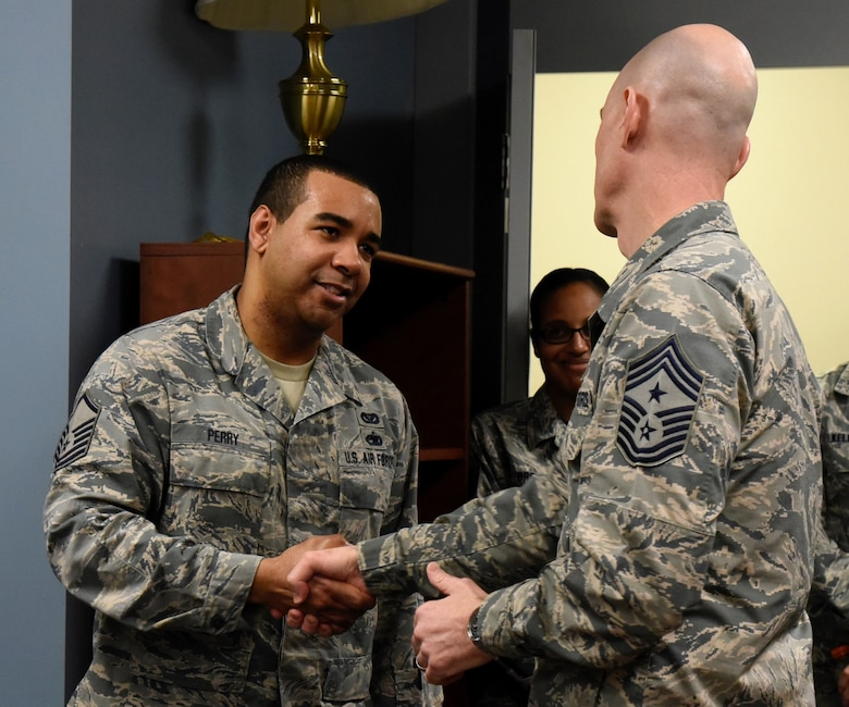 Command Chief Master Sgt. Ronald C. Anderson Jr., Command Chief Master Sergeant of the Air National Guard, coins Master Sgt. Dallas Perry, 235th Civil Engineering Flight program analyst, February 10, 2018 while touring Warfield Air National Guard Base, Middle River, Md.