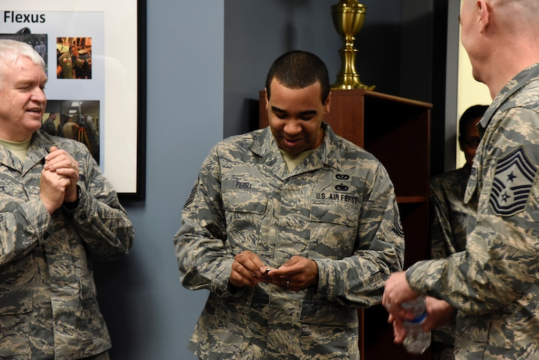 Master Sgt. Dallas Perry,  235th Civil Engineering Flight program analyst, observes the coin he just received from Command Chief Master Sgt. Ronald C. Anderson Jr., Command Chief Master Sergeant of the Air National Guard, and Lt. Gen. L. Scott Rice, the Director of the Air National Guard, February 10, 2018 at Warfield Air National Guard Base, Middle River, Md.
