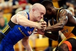 CAMP LEJEUNE, N.C. (Feb. 25, 2018) Marine Sgt. Raymond Bunker, from Villa Park, Ill., locks arms with his opponent during a match in the 2018 Armed Forces Wrestling Championship. Bunker is a member of the Armed Forces Sports program's All-Marines wrestling team. AFS All-Service teams provide servicemembers opportunities to participate in national and international competitions including the Military World Games and the Olympics. Servicemembers can advance to the All-Service level sports by competing in unit level intramurals through their branch's sports and fitness program. (U.S. Navy photo by Lt. Joe Painter)