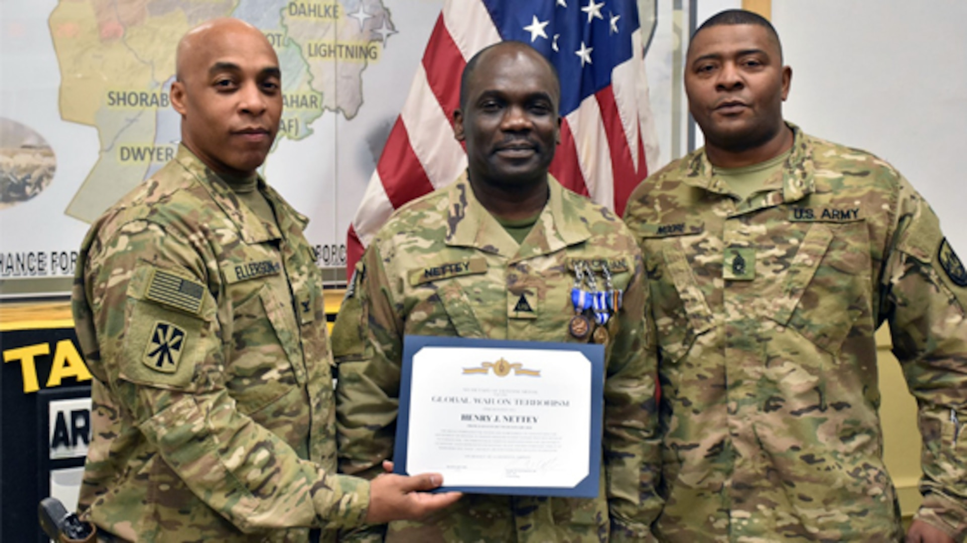 Army Col. James Ellerson, commander for the Area Support Group Afghanistan, and Army Command Sergeant Major Lloyd Moore, present Henry Nettey with the Global War on Terrorism medal and certificate, along with other accolades for his recent deployment. Nettey is currently a contract administrator at Defense Contract Management Agency Hampton in Virginia. (Photo courtesy of Don Baumgartner)