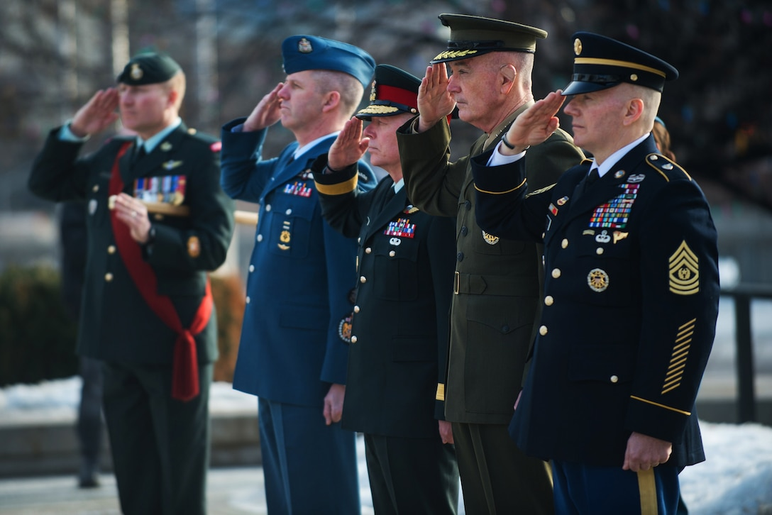 U.S. and Canadian defense leaders salute during a wreath-laying ceremony in Ottawa, Canada.