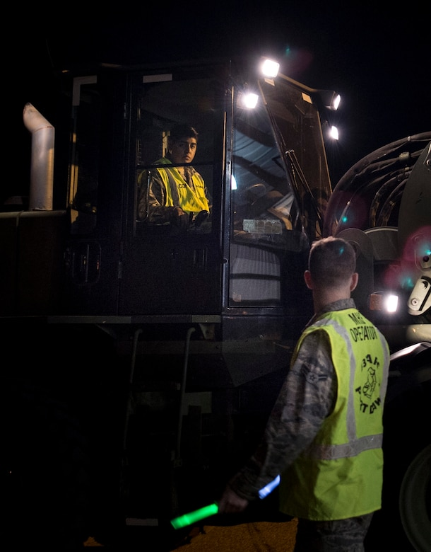 Airman 1st Class Benuel Harmon, 437th Aerial Port Squadron air transportation journeyman, guides Senior Airman Juan Rios, 437th APS forklift operator, through a cargo deployment function as part of mobility exercise Bold Eagle Feb. 26, at Joint Base Charleston, S.C.
