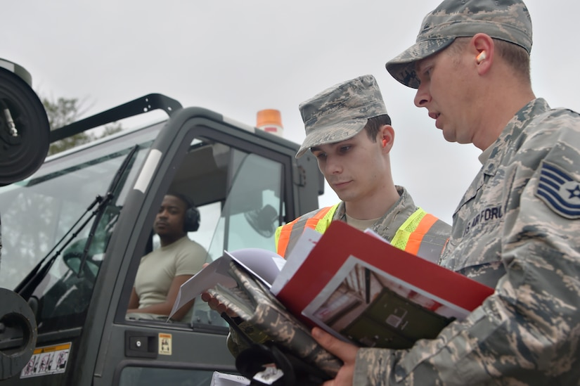 Airman 1st Class Tyler Connolly, center, 437th Aerial Port Squadron traffic management operations technician, and Tech. Sgt. Donovan Reid, right, 437th Aircraft Maintenance Squadron exercise chalk increment monitor, review a checklist during a simulated cargo inspection at a cargo deployment function as part of mobility exercise Bold Eagle Feb. 26, at Joint Base Charleston, S.C.