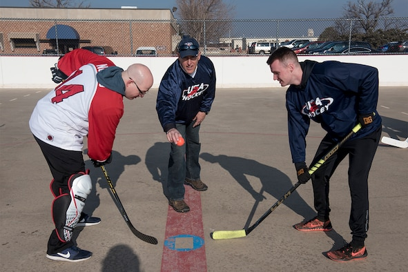 PETERSON AIR FORCE BASE, Colo. –  Robert Orwig 21st Space Wing Protocol Operations chief drops the ball to start the annual U.S. vs Canada Ball Hockey Game on Peterson Air Force Base, Feb. 23, 2018, Colorado.  The game consisted of three 15 minute periods, with the Americans coming out on top 3-2. (U.S. Air Force Photo by Airman 1st Class Alexis Christian)