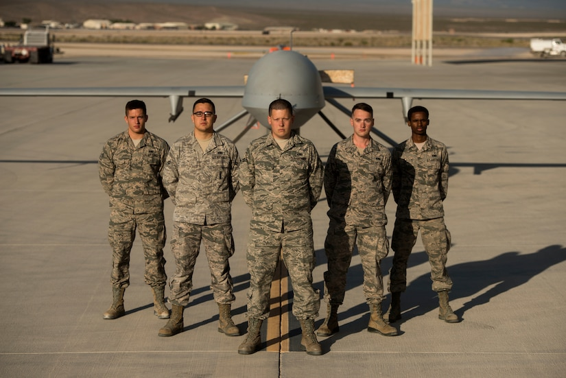 432nd Aircraft Maintenance Squadron maintainers stand in front of an MQ-1 Predator May, 5, 2015, at Creech  Air Force Base, Nev. The Predator is an armed multi-role Remotely Piloted Aircraft supporting combatant commander's downrange with persistent attack and reconnaissance capabilities. (U.S. Air Force photo by Tech. Sgt. Vernon Young Jr.)
