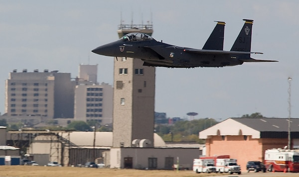 An F-15E Strike Eagle flies past the current air control tower at Joint Base San Antonio-Kelly Field, Texas Oct. 31, 2008.