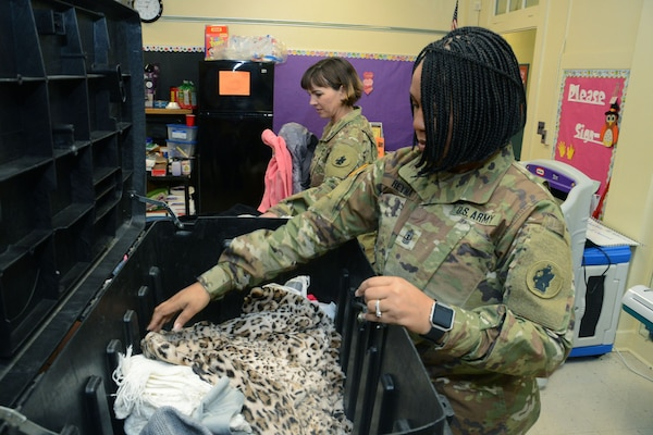 1st Sgt. Charmaine Reyna (right) and Capt. Debe Clark, Headquarters and Headquarters Battalion, U.S. Army South, at Joint Base San Antonio-Fort Sam Houston, sort through winter coats at Booker T. Washington Elementary School Feb. 22.  The company held a coat drive at U.S. Army South from Jan. 8 to Feb. 1, for the young students. The school and battalion are partnered through the Adopt-a-School program.