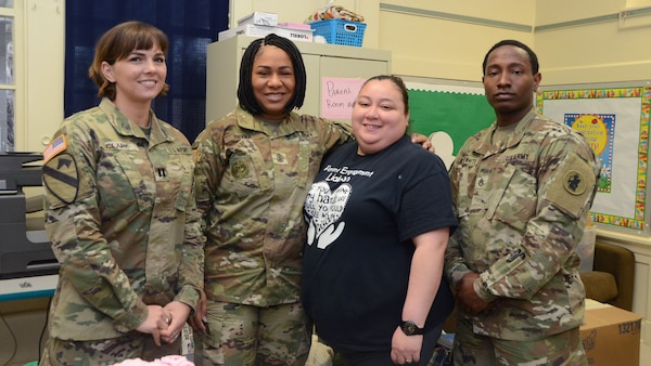Soldiers from Headquarters and Headquarters Battalion, U.S. Army South, take a photo with Julia Losoya, Parent and Family Liaison of Booker T. Washington Elementary School, after the Spartan Solders delivered boxes of winter coats to her classroom Feb. 22. The unit held a coat drive from Jan. 8 to  Feb.1, in support of the unit and school's partnership in the Adopt-a-School program.