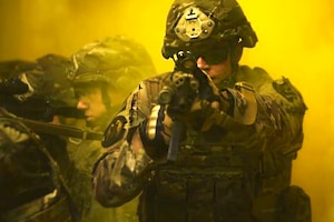 An airman holds a rifle while surrounded by yellow smoke.