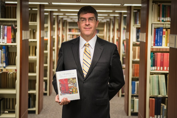 New MSFRIC director stands among the book shelves of the library.