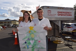 Leah and Evan Morgan, husband and wife team from Huntington District, U. S. Army Corps of Engineers, share the hand-drawn Christmas tree, sent to them by their Sunday school, age group 7 to 11, of First Missionary Baptist Church, Culloden, West Virginia. Leah, an administrative support assistant, deployed Nov. 14, and Evan, a civil engineer technician, joined her Dec. 22 to support the Corps Task Force Power Restoration mission.