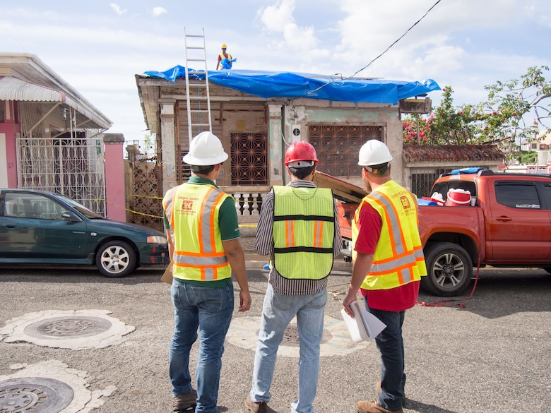 men evaluate blue roof installation