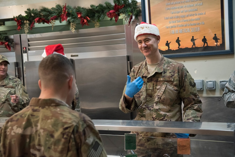 Chief Master Sgt. Ronald Anderson, Command Chief Master Sgt. of the Air National Guard, serves lunch to deployed military members at Al Udeid Air Base, Qatar, Dec. 24, 2017. Lt. Gen. L. Scott Rice, director of the Air National Guard, and Anderson visited deployed Air National Guardsmen at AUAB on Christmas Eve during a trip to the U.S. Central Command area of responsibility. (U.S. Air National Guard photo by Master Sgt. Phil Speck)