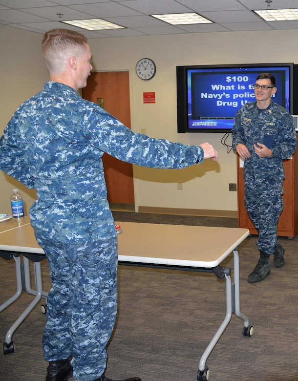 """Petty Officer 2nd Class Samuel Donovan, left, a hospital corpsman serving at Naval Health Clinic Charleston, answers a $100 question about the Navy's policy on drug use during NHCC's """"Impaired Driving Month Jeoparody Challenge"""" Dec. 20, 2017 at NHCC."""