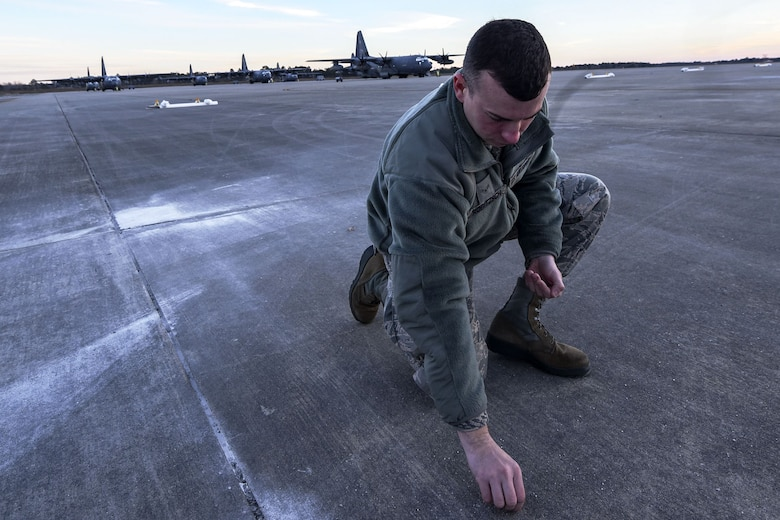 Senior Airman Reed Robitzsch, 23d Maintenance Squadron aircraft structural maintenance journeyman, picks up debris off the flight line during a foreign object debris (FOD) walk, Jan. 2, 2018, at Moody Air Force Base, Ga. The FOD walk was performed following the winter holidays to remove any debris that could potentially cause damage to aircraft or vehicles. (U.S. Air Force photo by Airman Eugene Oliver)