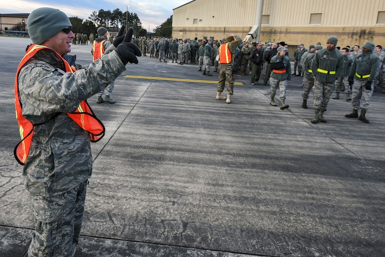 Tech Sgt. Christopher Edmonson, 23d Maintenance Group quality assurance inspector, signals Team Moody Airmen during a foreign object debris (FOD) walk, Jan. 2, 2018, at Moody Air Force Base, Ga. The FOD walk was performed following the winter holidays to remove any debris that could potentially cause damage to aircraft or vehicles. (U.S. Air Force photo by Airman Eugene Oliver)