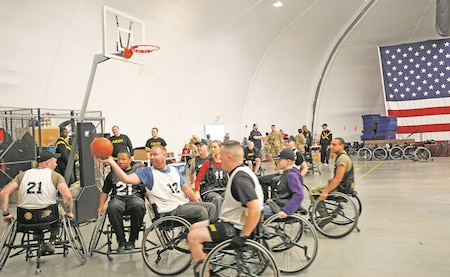 Corey Wright, center, Wounded Warrior Project coordinator, holds the ball and participates in the seated wheelchair basketball game for Warrior Care Month. The game took place at WTB gym Building 405 on Nov. 22. This sporting event allowed the Soldiers to use their physical endurance by moving the wheelchair through hand coordination.