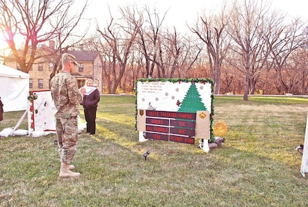 Garrison Command Sgt. Maj. James Collins evaluates a giant holiday card created by personnel of the Directorate of Plans, Training, Mobilization and Security Nov. 30 at Ware Parade Field in front of garrison headquarters.
