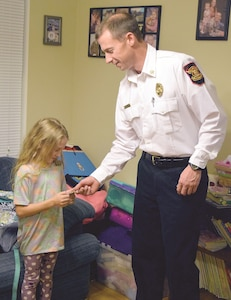 Karyna Baker, 11, left, daughter of chief Warrant Officer 2 Joseph Baker 3rd Assault Helicopter Battalion, 1st Aviation Regiment, 1st Combat Aviation Brigade, 1st Infantry Division, receives a coin from Fire Chief Ric Seward, Fort Riley Fire and Emergency Services, Nov. 29 at her home for reporting a fire in her garage.