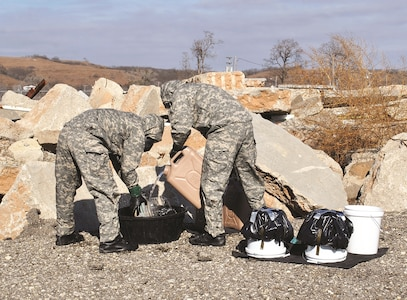 First Lt. Austin Schultz, left, 774th Ordnance Company, 242nd Ordnance Battalion, 71st Ordnance Group (Explosive Ordnance Disposal), holds a leaking landmine while Pfc. Jeremy Poe, 774th Ord. Co., pours water over it during a chemical incident response training Nov. 29 at the Fire Department Training Site on Camp Funston. Following the rinse, Schultz scrubbed the device for five minutes before he and Poe sealed the leak and secured it for transport.
