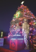 Command Sgt. Maj. Joseph Cornelison, left, 1st Infantry Division senior noncommissioned officer, and Maj. Gen. Joseph M. Martin, 1st Inf. Div. and Fort Riley commanding general, turn to admire the bright lights of the Fort Riley holiday tree lights Dec. 1 on Ware Parade Field.