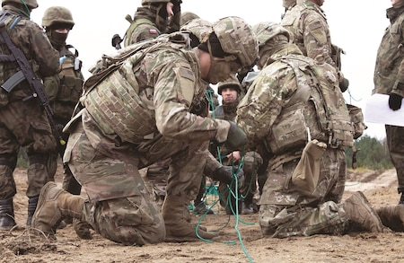 Polish soldiers with the 2nd Engineer Battalion, 5th Engineer Regiment, and U.S. Soldiers with the 82nd Brigade Engineer Battalion, 2nd Armored Brigade Combat Team, 1st Infantry Division, practice laying out detonation cord to attach to explosive charges at the Drawsko Pomorskie training area during a 13-day training event called Bull Eagle near Oleszno, Poland, Nov. 27. The 2nd ABCT helps assure NATO allies and deter aggression by demonstrating and sustaining maximum proficiency and readiness in its warfighting functions, tasks and drills by conducting training with U.S. allies throughout a strong Europe.