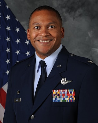 Offical Air Force photo of Col. Rhone with U.S. flag in background
