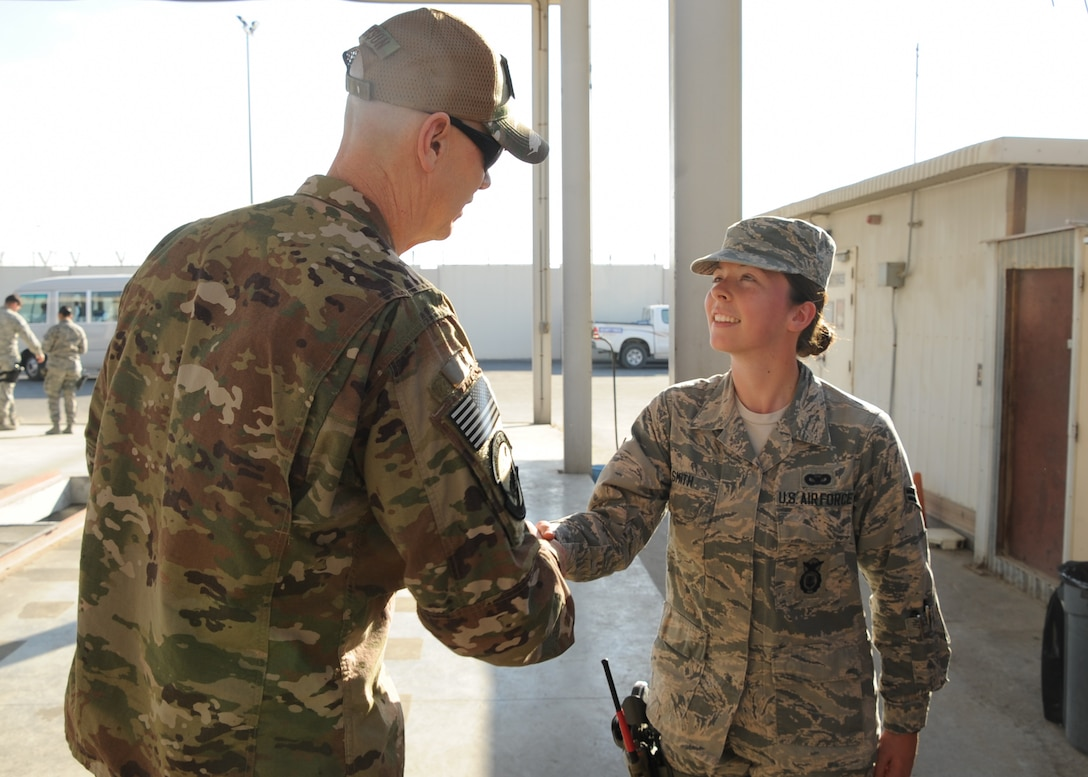 Chief Master Sgt. Ronald Anderson, command chief master sergeant of the Air National Guard coins Airman 1st Class Rachel Smith, 380th Expeditionary Security Forces Squadron, installation entry controller, during his visit to Al Dhafra Air Base, United Arab Emirates Dec. 26, 2017. Smith is deployed from the 166th Airlift Wing, New Castle Air National Guard Base, Delaware.