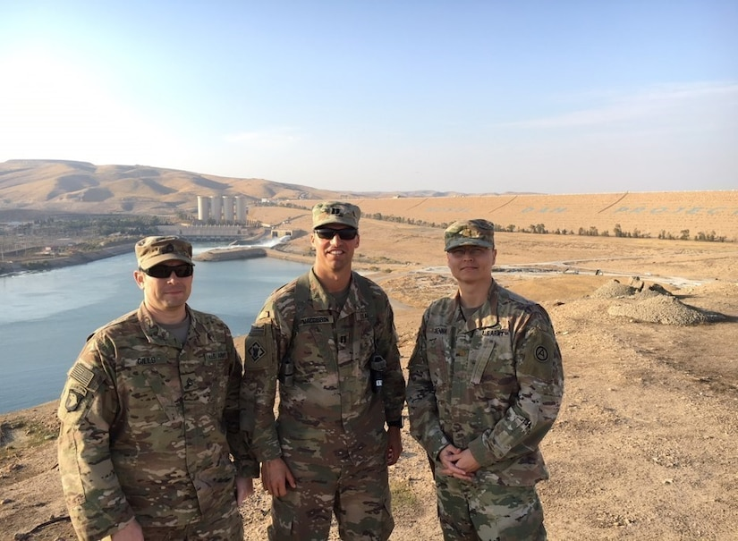 Three Soldiers standing in front of a dam.