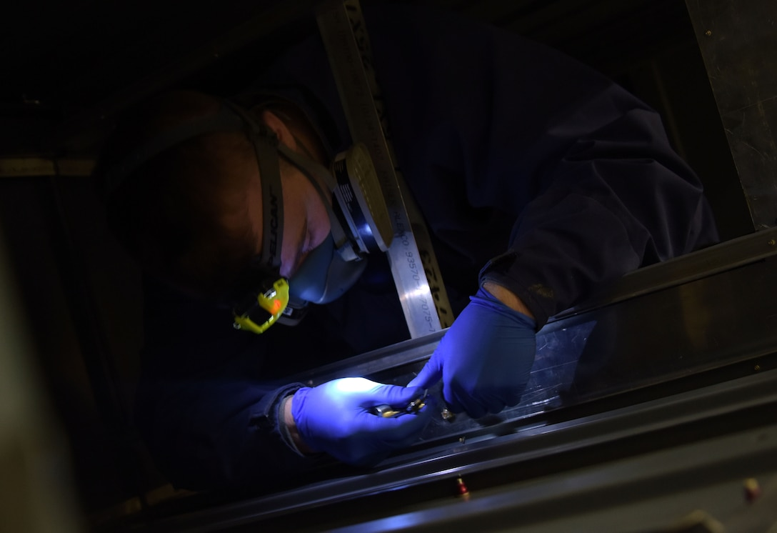 U.S. Air Force Airman Shawn Bragg, 100th Maintenance Squadron aircraft fuel systems apprentice, secures bolts inside the confined space trainer Dec. 15, 2017 on RAF Mildenhall, England. The conditions inside an actual wing fuel-tank are simulated inside the training unit to prepare Airmen. Trainees are required to wear personal protective equipment just as they would operationally.  (U.S. Air Force photo by Senior Airman Justine Rho)