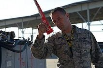 """U.S. Air Force Master Sgt. Christopher Schneider, F-16 Viper Demonstration Team superintendent, inspects a """"Remove Before Flight"""" warning ribbon attached to an F-16CM Fighting Falcon during a Proud Falcon Competition at Shaw Air Force Base, S.C., Dec. 21, 2017."""