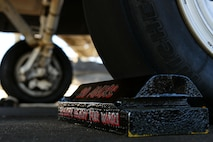 A chock rests in front of an F-16CM Fighting Falcon tire during a Proud Falcon Competition on the flightline at Shaw Air Force Base, S.C., Dec. 21, 2017.