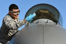 U.S. Air Force Staff Sgt. Pedro Cahua, 20th Aircraft Maintenance Squadron, 79th Aircraft Maintenance Unit, dedicated crew chief, cleans the canopy of an F-16CM Fighting Falcon before judges review the aircraft for a Proud Falcon Competition at Shaw Air Force Base, S.C., Dec. 21, 2017.