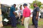 Technicians of the Dominica Fire Service inspect one of the generators sent in from DLA Disposition Services at Crane, Indiana, in preparation for transporting it to the fire station at Dominica's lone international airport.