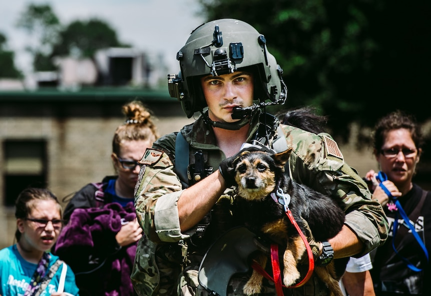 Senior Airman Austin Hellweg, 129th Rescue Squadron special missions aviator, carries a dog and leads a family into an HH-60 Pavehawk for extraction to a safer location during the relief effort for Hurricane Harvey, Aug. 31st, 2017, Beaumont, Texas. The relief efforts have a conglomerate of active, guard and reserve units from all branches aiding the federal government to help Texas recover from Hurricane Harvey. (U.S. Air Force photo by Staff Sgt. Jordan Castelan)