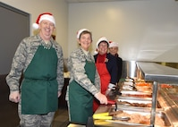 Gen. Pawlikowski, Lt. Gen. McMurry, and Ms. Young preparing to serve dinner.