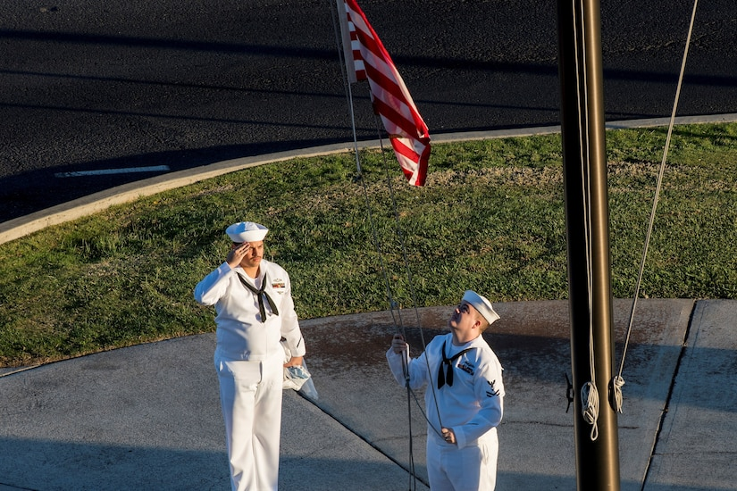 """Navy Petty Officer 2nd Class Gerado Taddei, left, and Petty Officer 2nd Class Andrew Thompson fly the """"First Navy Jack"""" to start the New Year on Joint Base Pearl Harbor-Hickam, Hawaii, Jan. 1, 2018."""