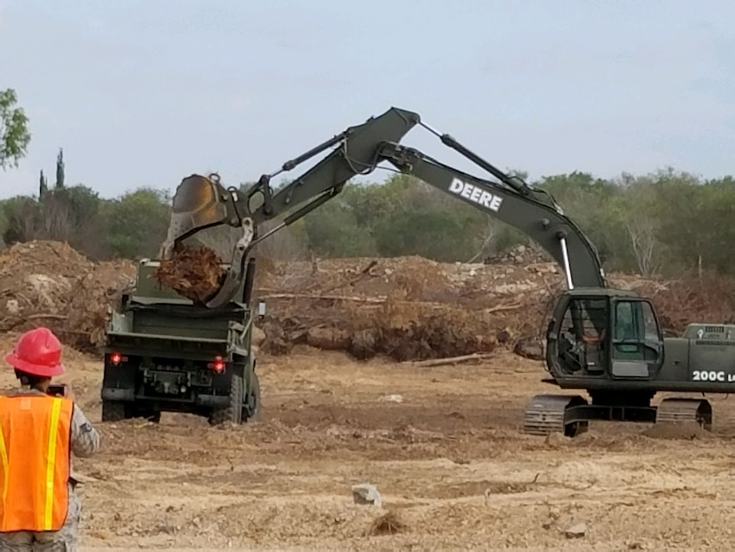 Members of the 219th RED HORSE Squadron of the Montana Air National Guard operate heavy equipment to improve water drainage near buildings located on an Israeli Defense Force base. (U.S. Air National Guard photo)